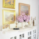 white cabinet paired with gold fraims and purple hydrangeas