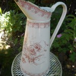 A stunning white body pitcher with a red floral motif. This is an earlier piece, late 1800s to early 1900s, and unusual in that it has decoration around the lip of the pitcher.