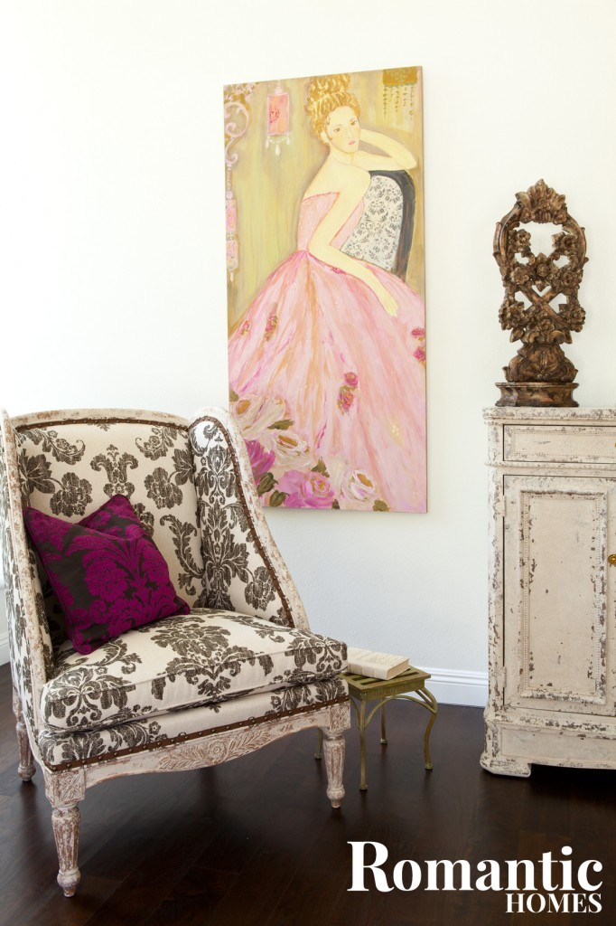 A black and white damask arm chair in front of a painting of a dancer by artist Susan Brown