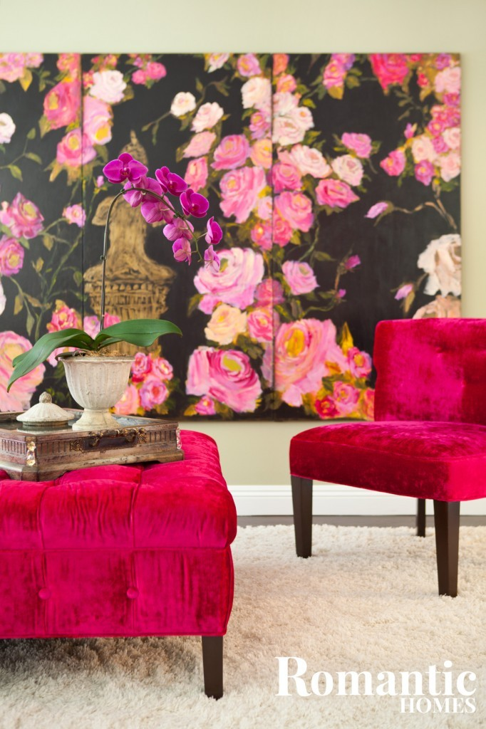 A chair and ottoman upholstered in dark pink sit in front of a large floral artwork