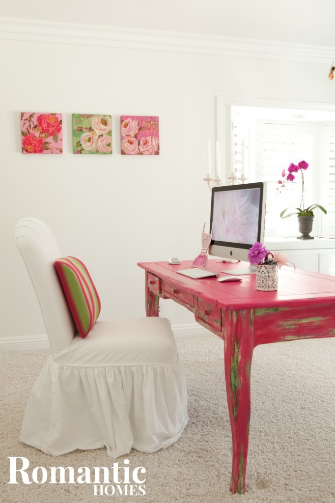An all white office is brightened up by the shabby bright pink desk