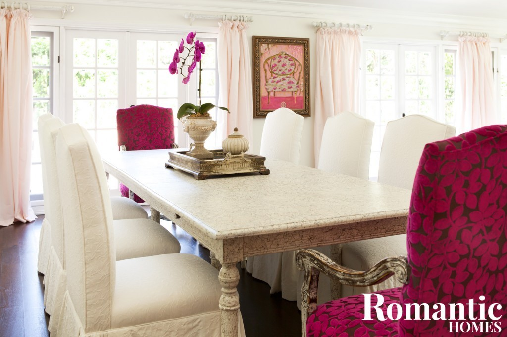 A dining room table surrounded by white and dark-pink chairs