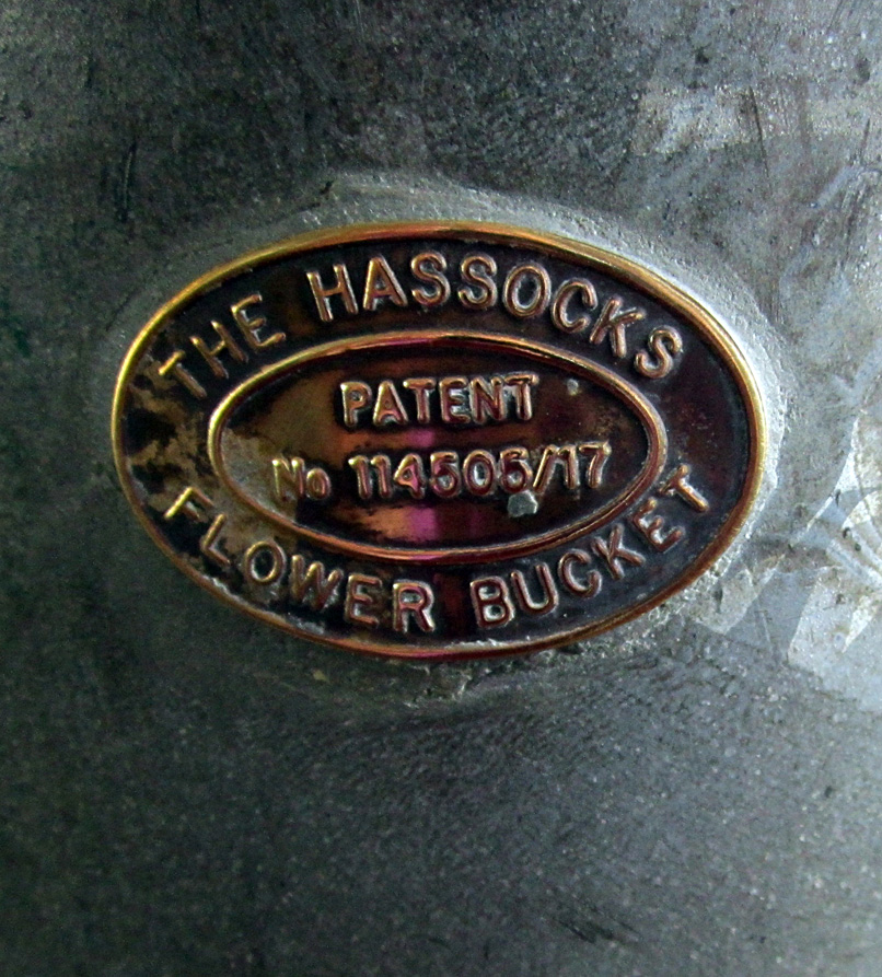 "Metal label on galvanized flower bucket that reads ""The Hassocks Flower Bucket - Patent No. 114505/17"""