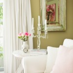 Shabby chic style with green walls, white furniture and pink cushions