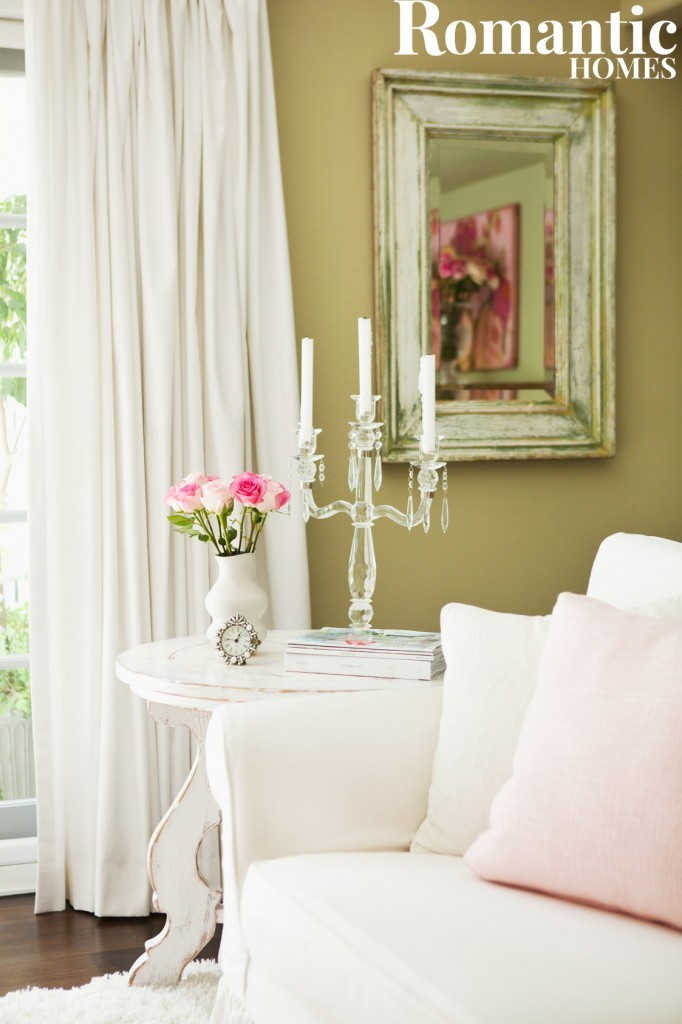 Decorating for spring in shabby chic style with green walls, white furniture and pink cushions