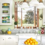 kitchen with white cabinets, green walls, farmhouse sink, lemons on counter