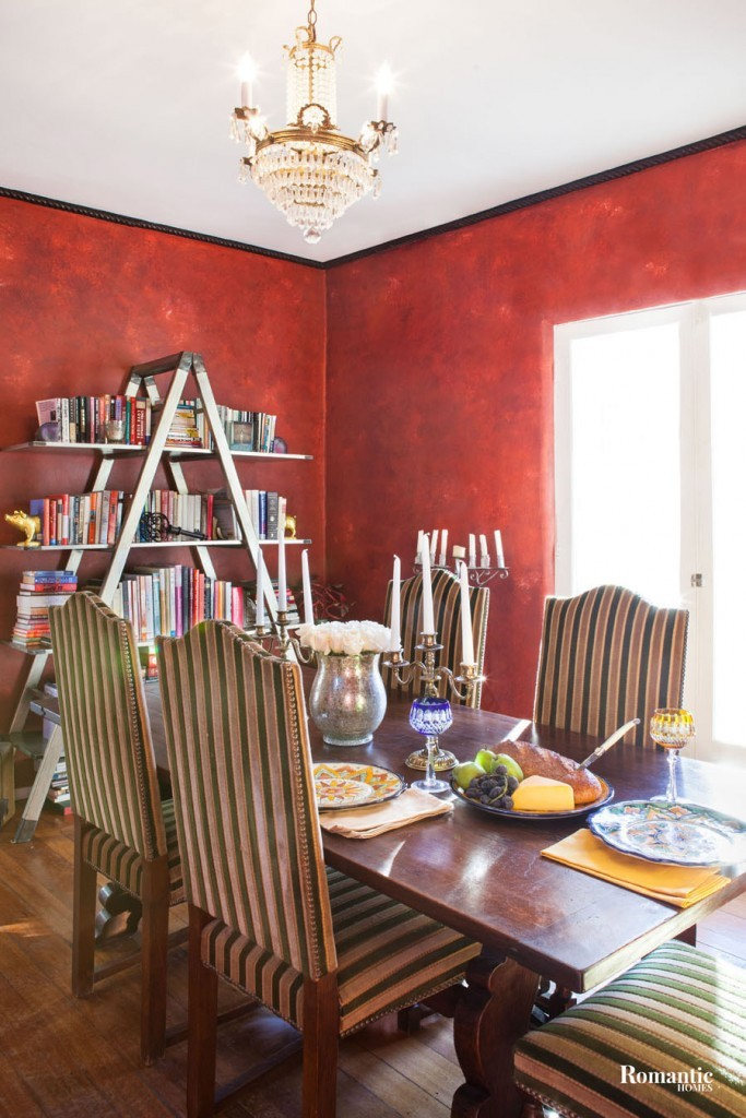 Jennifer selected the striking red wall color to complement the home's Spanish architectural style. The bookshelf goes with the desk in the loft but was too large for the space, so it gives an industrial punch to the dining room. A mix of vintage finds dresses up the room.