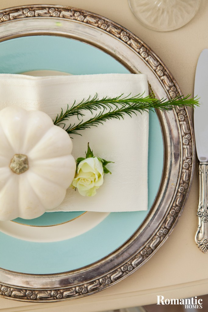 In her dining room, Amy decorates for fall with appropriate white pumpkins and sprigs of green.