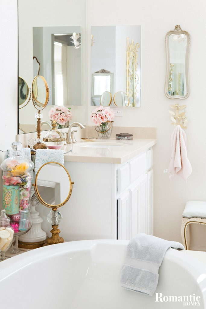This tract home bathroom gets a vintage makeover with a farmhouse style bathtub and vintage bathroom accessories.