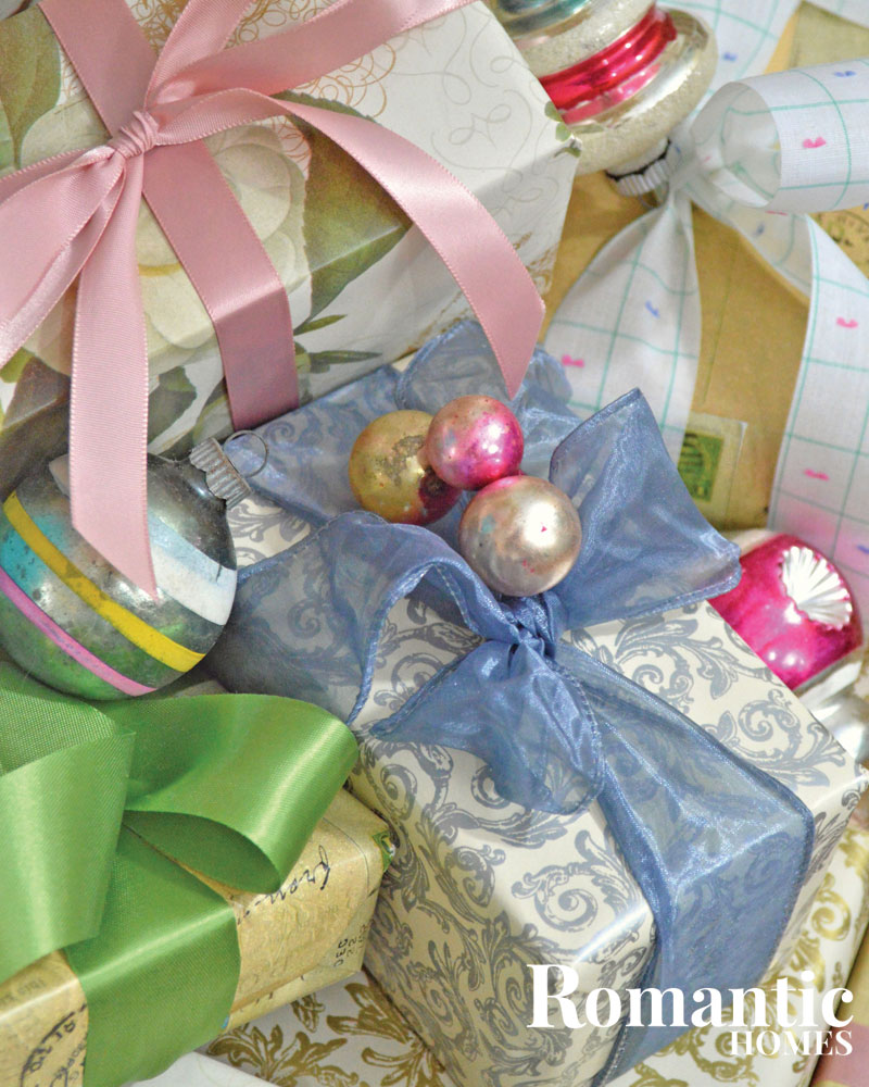 Christmas presents wrapped in silver and gold paper with pastel bows and ornament gift toppers