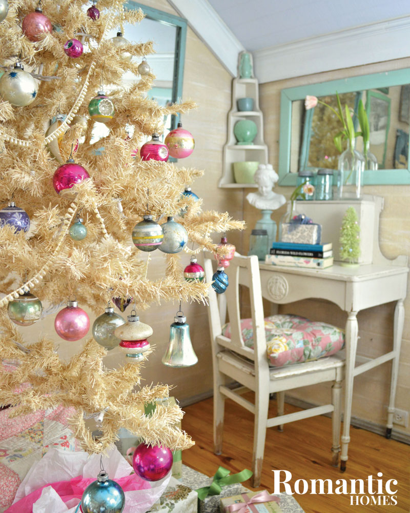 A white artificial tree with pink and aqua ornaments sits near a white writing desk.