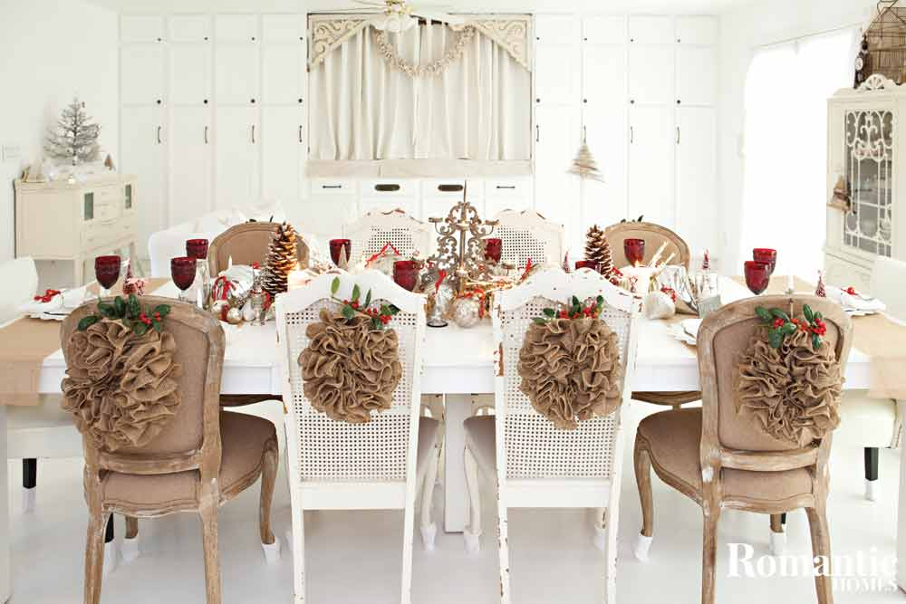 Christmas dinner table with mix of white and brown chairs and rustic decor.