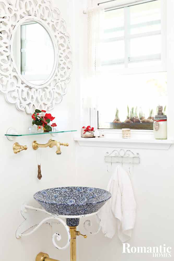 All white bathroom with ornamental mirror over a blue and white basin.