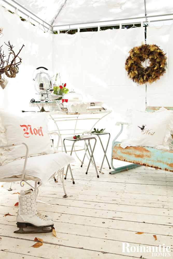 An enclosed porch with rustic furnishings and holiday decor.