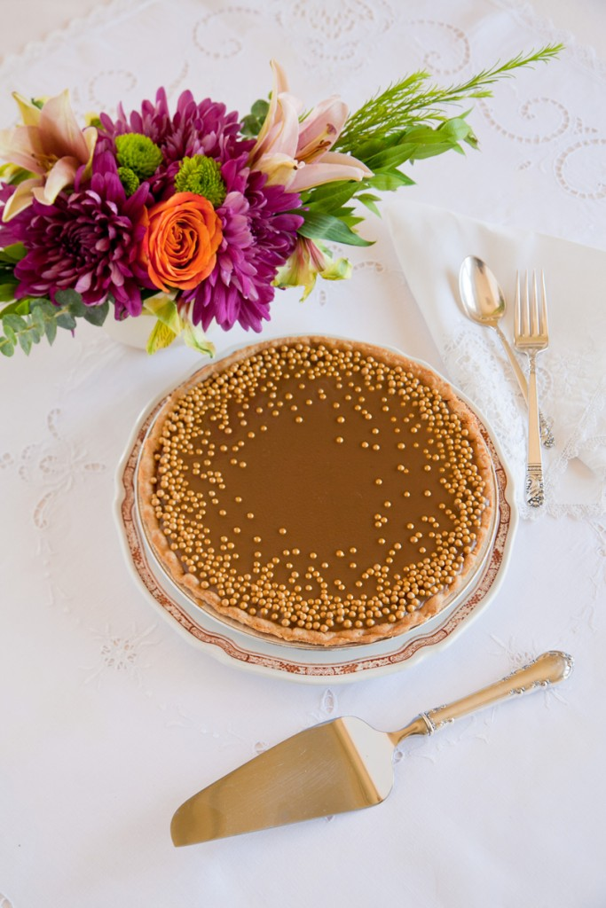 Pumpkin pie with bourbon caramel topping and gold dragées.