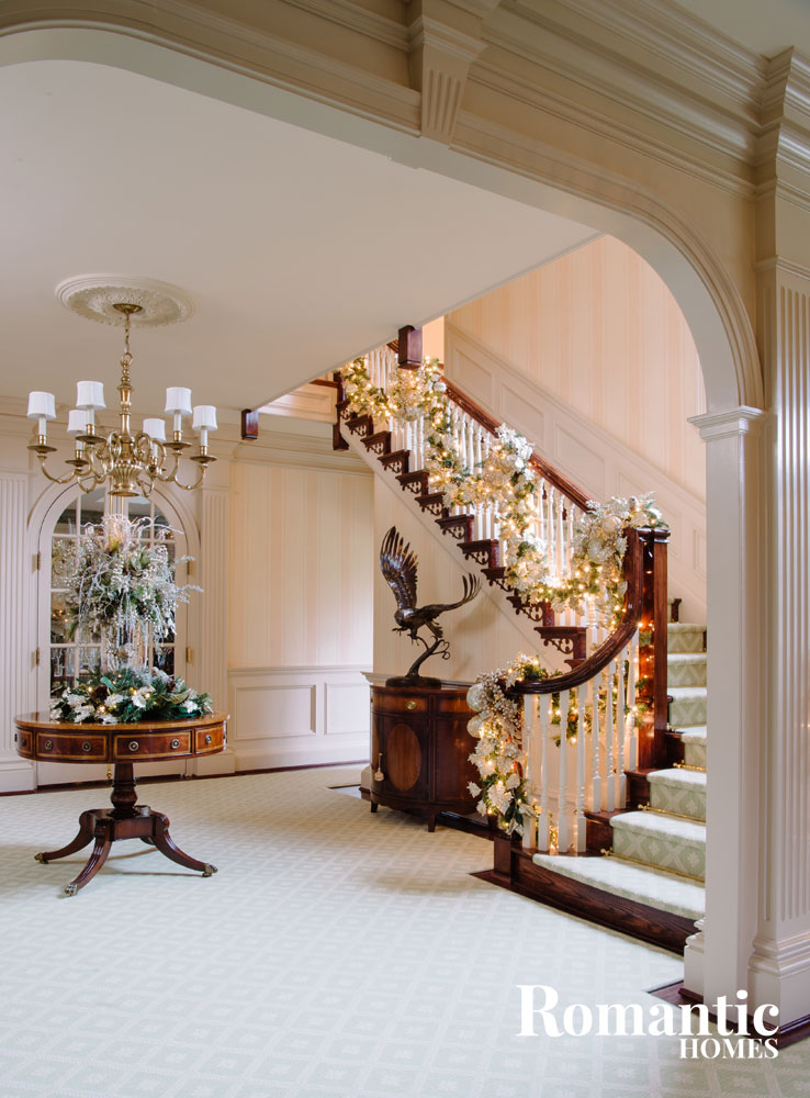 This large foyer required a striking focal point that sets the tone for the entire home. The grand staircase is bedecked with an equally impressive garland.