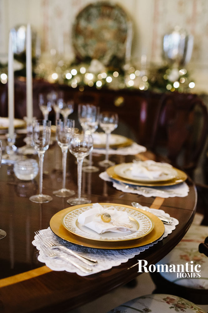 Dining table set with white and gold dishware and crystal