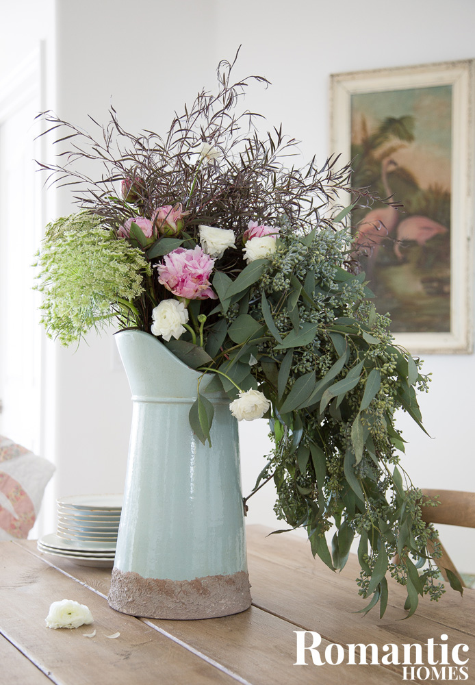 Romantic bouquet of peonies, eucalyptus and agaonis in teal enamelware pitcher