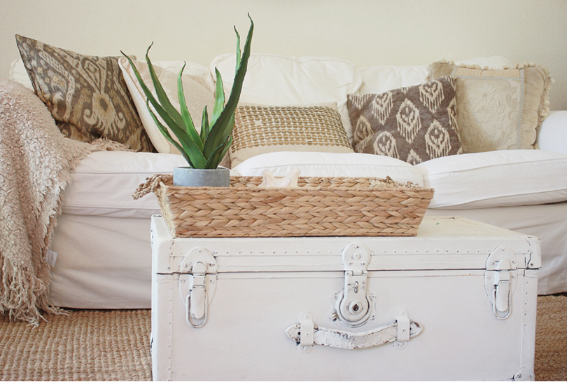 White slip-cover sofa and painted trunk coffee table