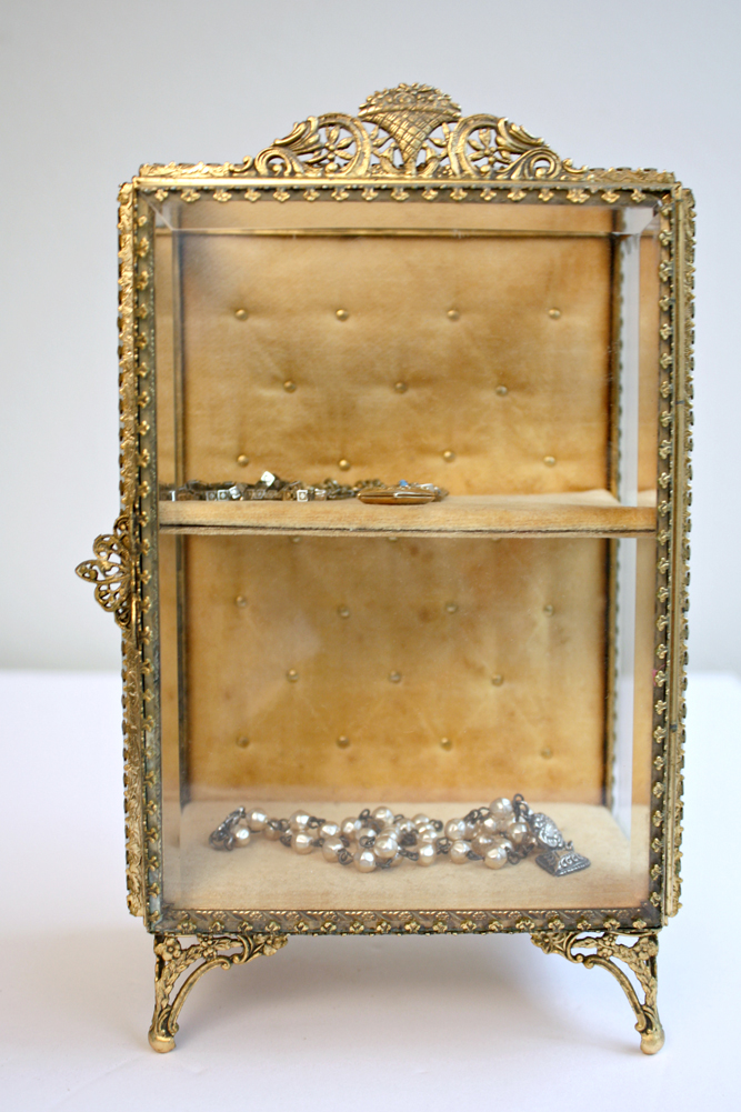 Upright glass jewelry casket lined with gold tufted velvet