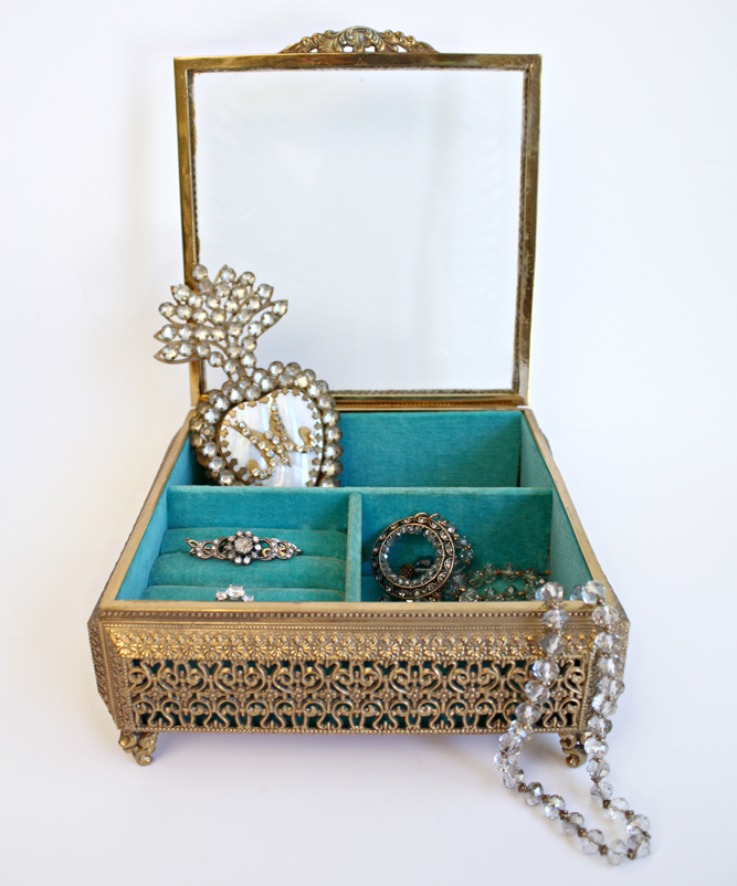 Vintage gold colored jewelry casket lined with teal velvet