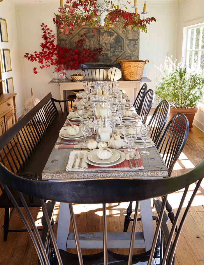 Nora Murphy's European garden-themed dining room has a simple and elegant look for fall. Live maple leaves and branches add color to the otherwise neutral palette. An antique bee skep and 18th century European mural grace the room with history.