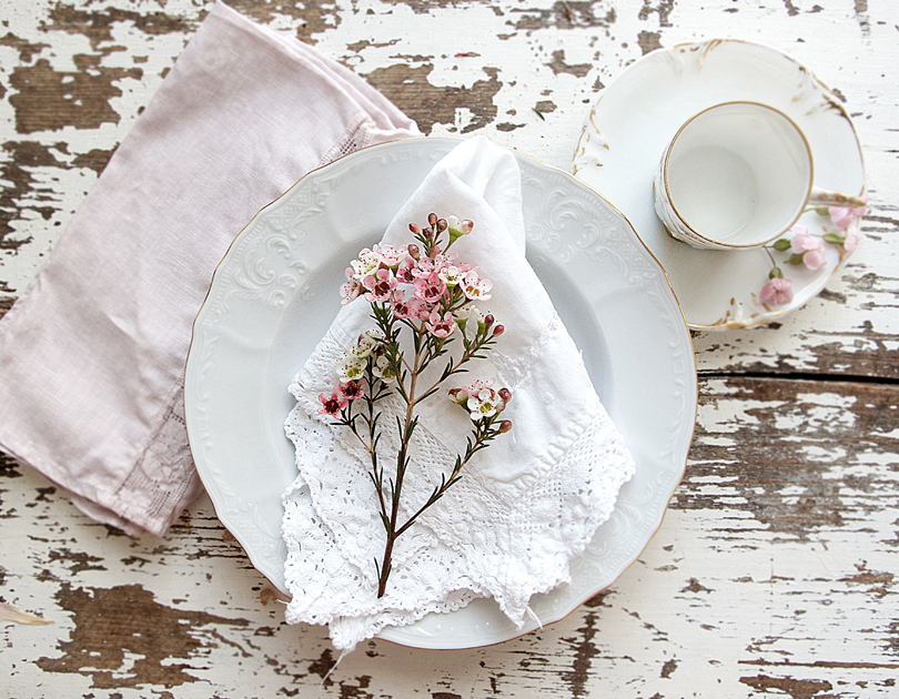 A beautifully aged patina with chipped paint contrasts beautifully to the delicate place setting.