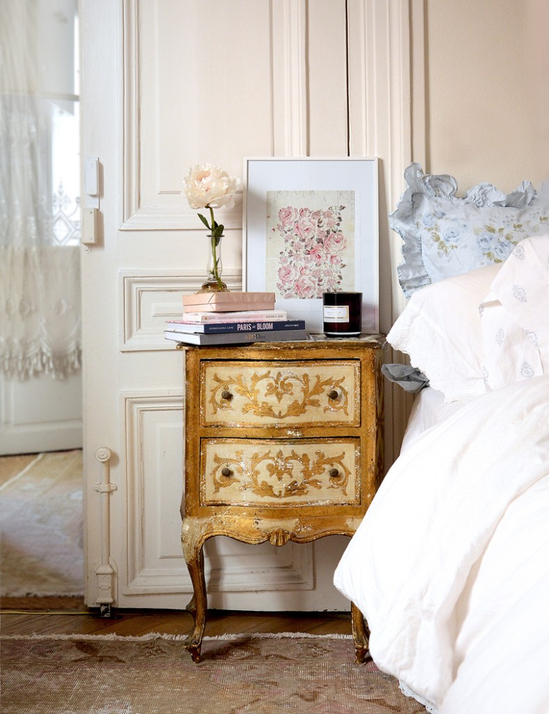 Though most of the color palette includes whites, soft pinks and blues, this gold nightstand fits perfectly with the decor.