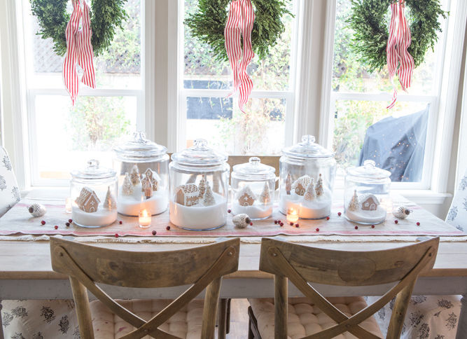 Gingerbread houses are nestled in apothecary jars like snow globe scenes for the tabletop.