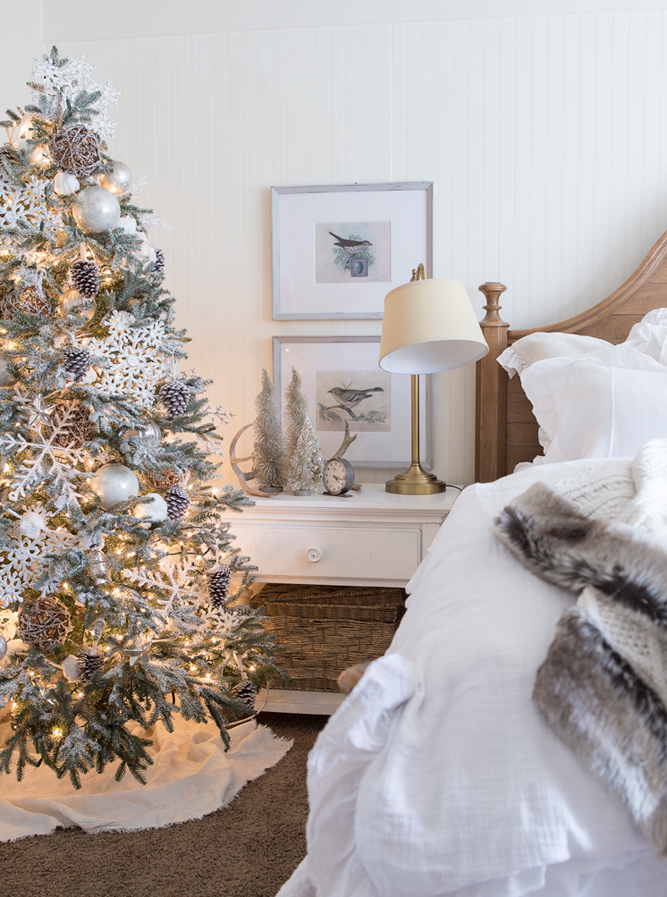 A flocked Christmas tree gives the bedroom a cozy woodland feel.