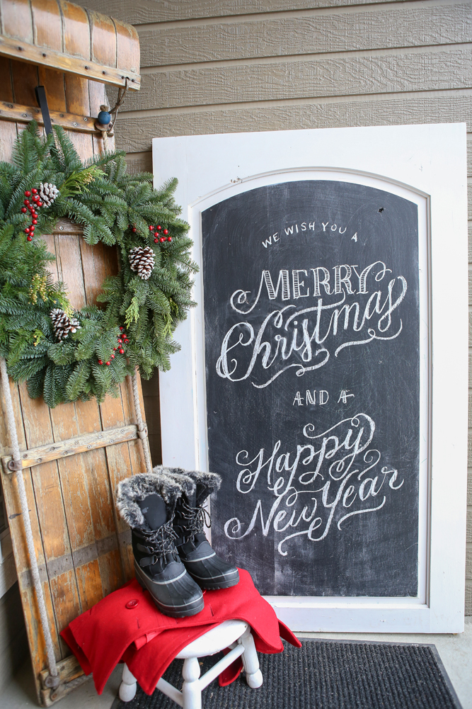 Holiday porch with antique sled and chalkboard sign