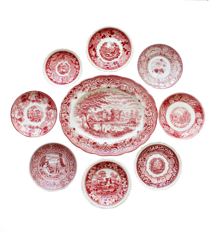 A display of red transferware plates and a platter