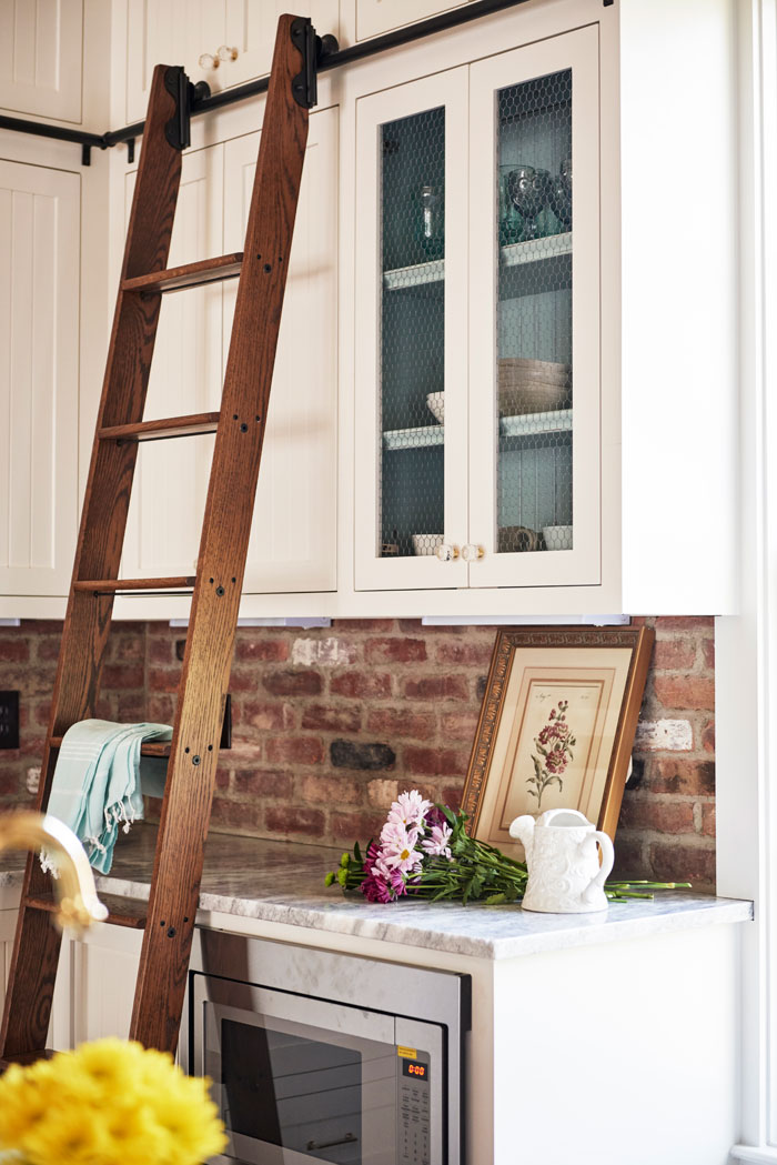 Library ladder in the kitchen allows homeowners to reach upper shelves