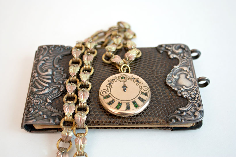 An antique locket on a chain of Black Hills gold
