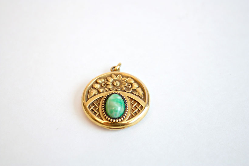 Set with a semi-precious stone, this round locket is bright and cheerful, with a floral design on the front.