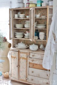 Rachel Ashwell's hutch is covered in whimsical wallpaper and full of mismatched dishes.