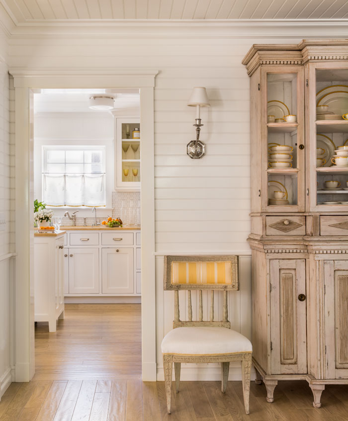Vertical wainscoting and horizontal wood paneling offer a unique, yet traditional texture to the walls. Particularly when paired with the paneled ceiling, crown molding and entry casings.