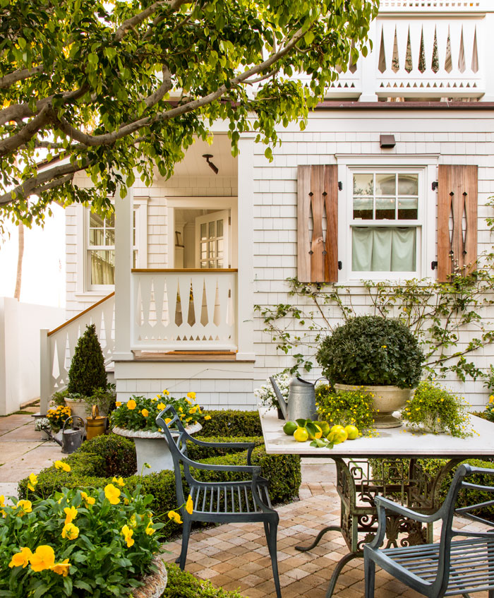The home's yellow color palette extends outdoors to the patio area with bright blooms on in potted plants