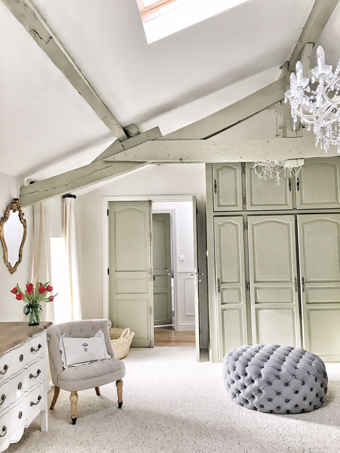 A pale green/gray shade highlights the old home's woodwork and ceiling beams.