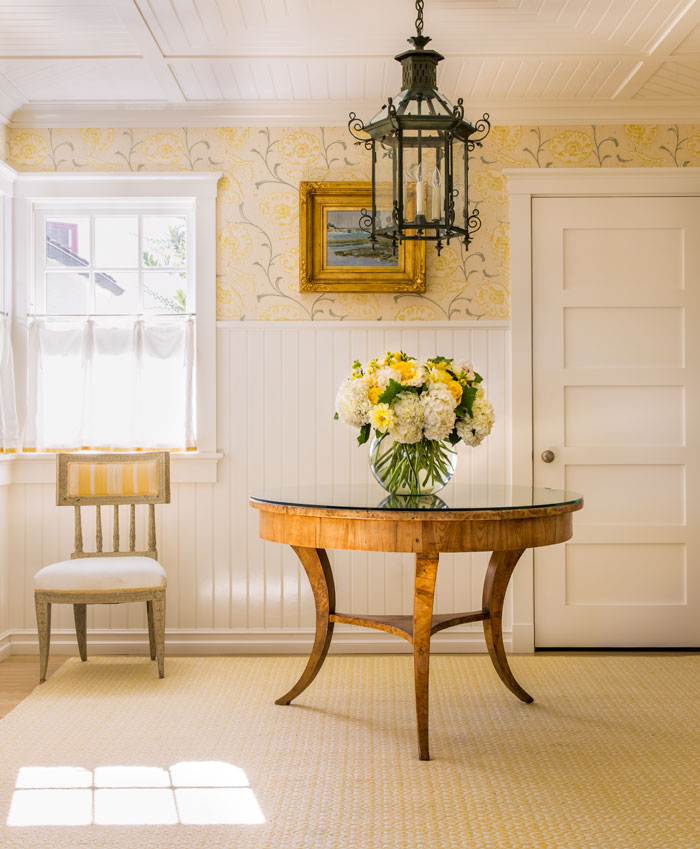 Yellow wallpaper, white wainscoting and antique furnishings create a welcoming entryway.