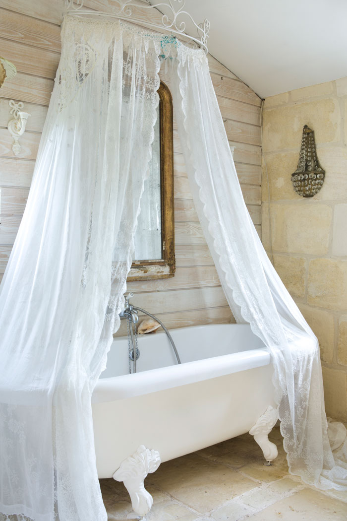 Marie-Caroline chose a lacy fabric to surround the bathtub instead of the typical shower curtain. Behind the bathtub, a wall of cerused wood adds another level of texture to the space.