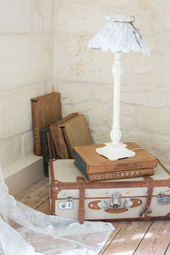 A lamp stand assembled from antique books and a vintage suitcase