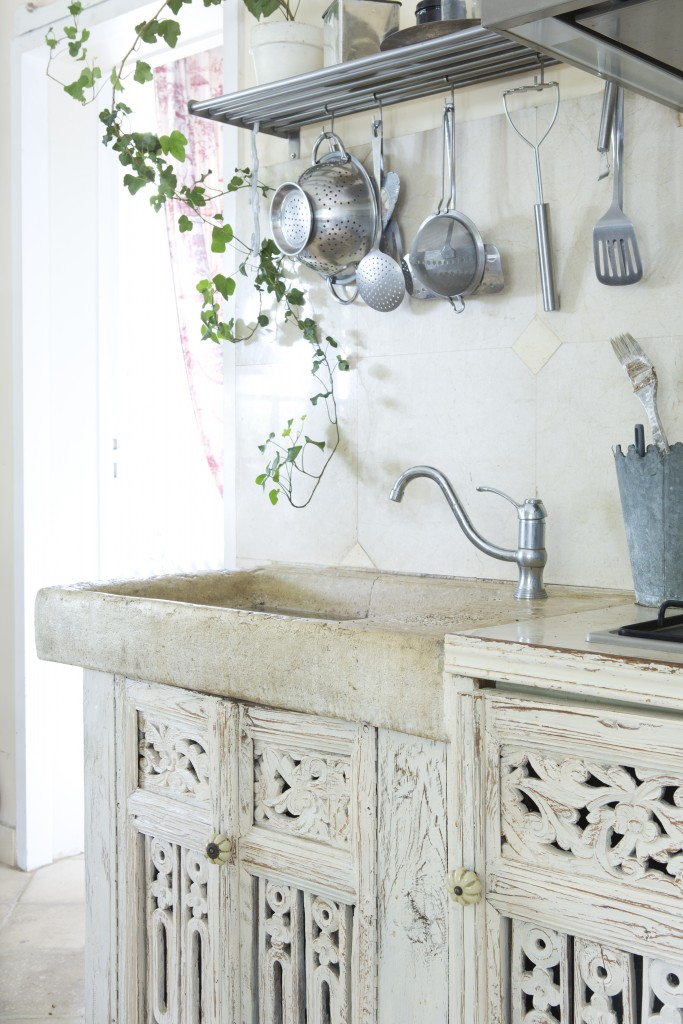 A stone skink basin sits above carved cabinet doors with a white-washed and worn patina in this shabby vintage French kitchen.