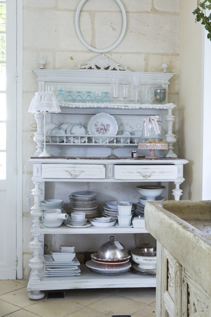 An ornately carved sideboard painted in blue-gray provides extra storage for kitchen necessities.