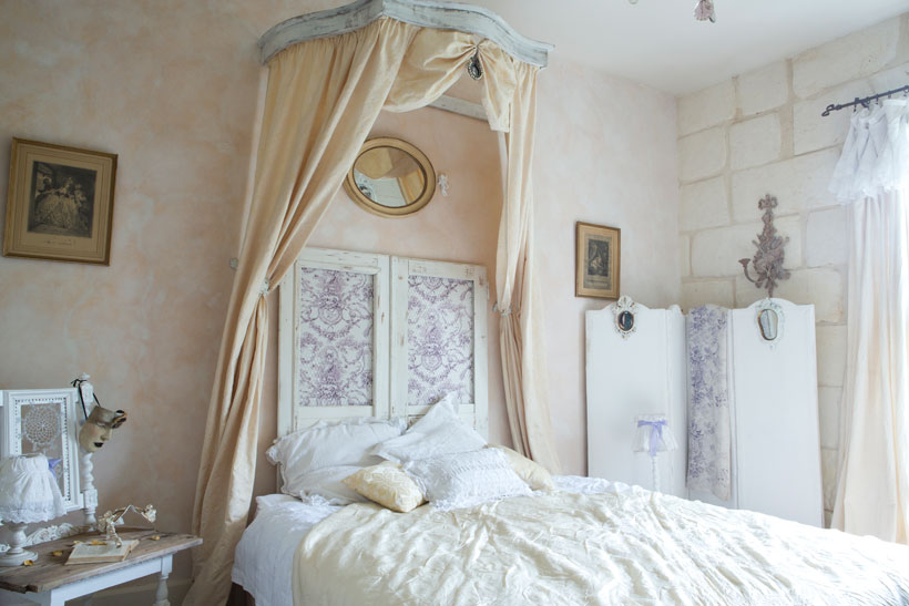 A pair of antique and weather-worn salvaged doors create a headboard behind the bed. Purple toile fabric was added to the insets as a fresh update. A swath of the same pattern hangs from the center of the dressing screen.