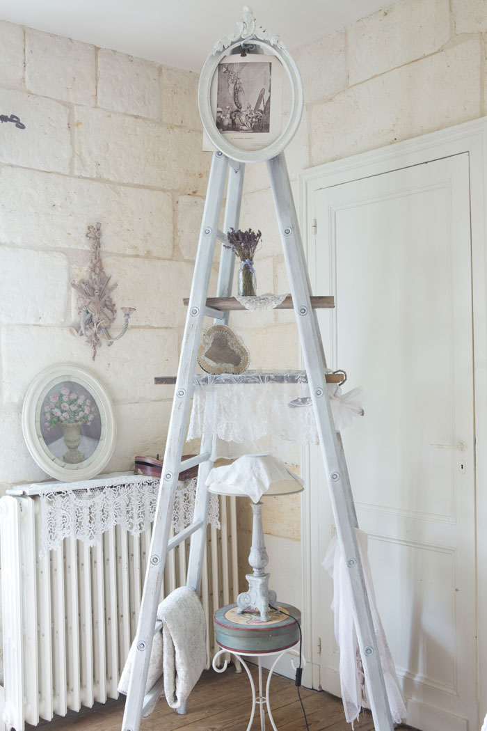 A white ladder acts as makeshift shelving on the upper rungs, with the lower providing a convenient spot to hang blankets.
