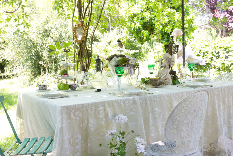 A lush setting, lacy details and vintage accessories create a whimsical atmosphere in Marie-Caroline's backyard in the French Bordeaux region.