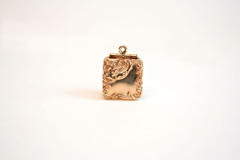 Rare to find, this square double-sided gold locket features a raised relief design of rococo scrolls and a mythical griffin.