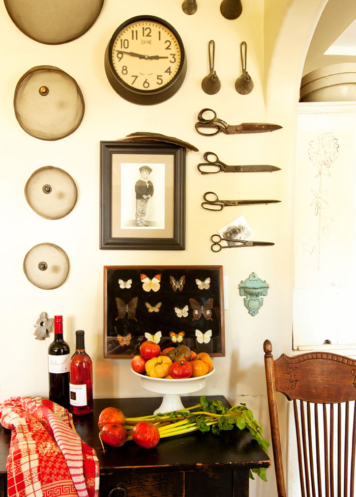 Kaari transformed one of her kitchen walls to display an eclectic collection of antique items, including scissors, butterflies and kitchenware.