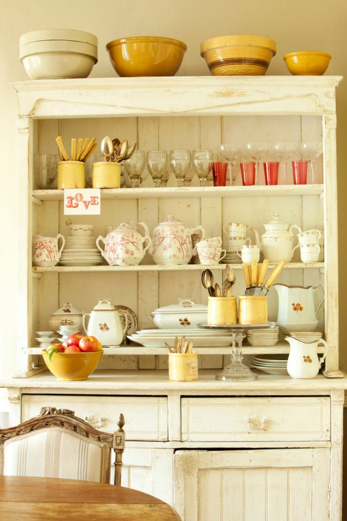 An assortment of beautiful kitchenware is displayed in the French armoire's open shelving. Pops of country colors like yellows and reds in the delicate china sets keep with the home's color palette.